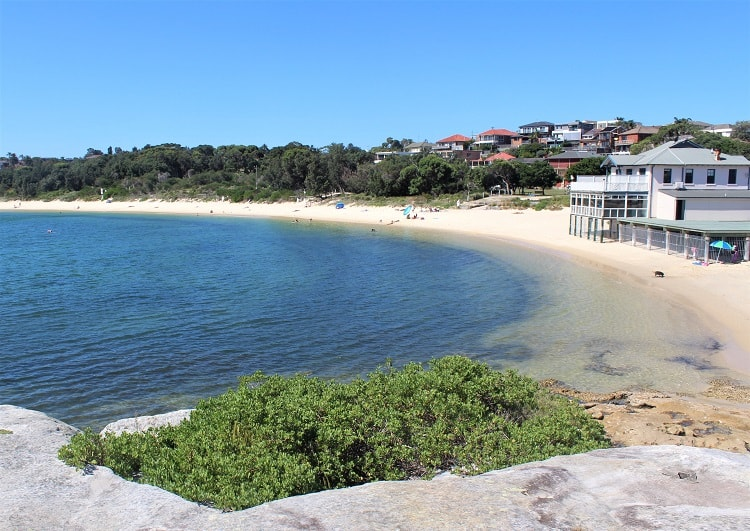 Looking down on bright white La Perouse Beach on a sunny day in Sydney.