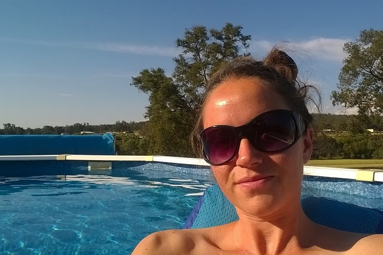 A female backpacker in a swimming pool at a luxury house sit near Perth, Western Australia.
