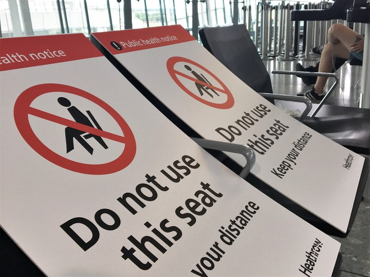 Signs on seats at Heathrow Airport ensuring passengers social distance and don't sit close together.