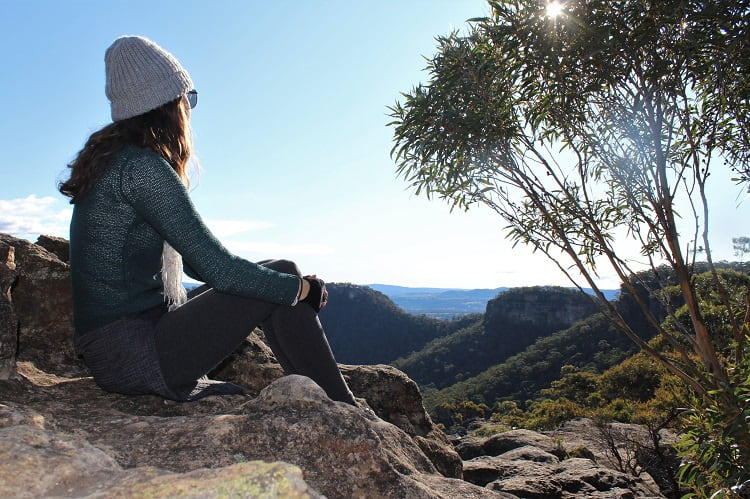 Female travel blogger admiring the view of the Blue Mountains from Sunset Rock in Mount Victoria.